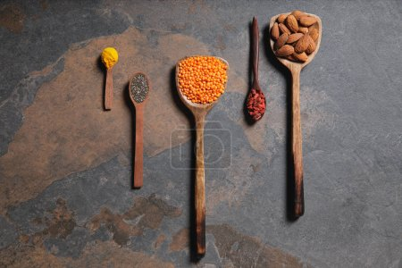Photo for Top view of arranged wooden spoons with superfoods, red lentils and turmeric on table - Royalty Free Image
