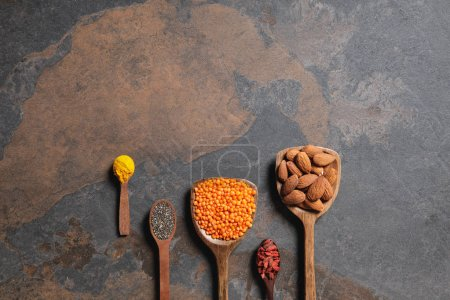flat lay of arranged wooden spoons with superfoods, red lentils and turmeric on table with copy space
