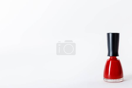 bottle of bright red nail polish on white