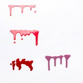 top view of dripping spills of shiny nail polish isolated on white