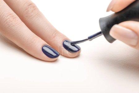 Photo pour Manucure femme appliquant bleu marine vernis à ongles sur les ongles de femme sur fond blanc - image libre de droit