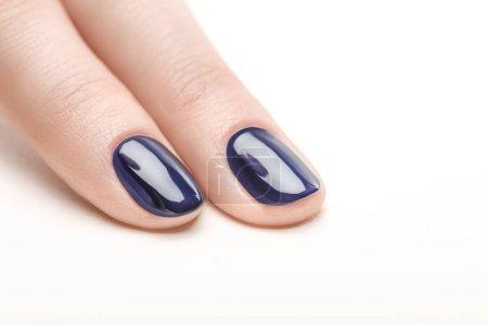 Photo pour Ongles avec des vernis à ongles bleu marine brillant sur fond blanc - image libre de droit