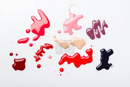 top view of abstract spills of nail polish with drops isolated on grey