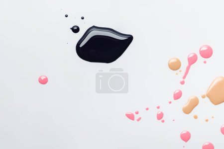 Photo for Top view of wet black spill with pink and beige drops isolated on grey - Royalty Free Image