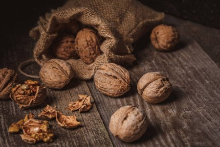 Photo for Close up view of walnuts in sack on wooden background - Royalty Free Image
