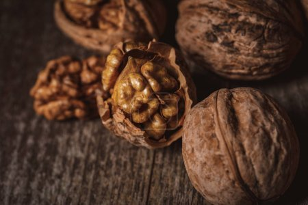 Photo for Close up view of shelled and whole walnuts on wooden tabletop - Royalty Free Image