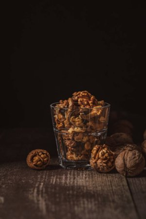 Photo for Close up view of shelled walnuts in glass on wooden tabletop on black background - Royalty Free Image