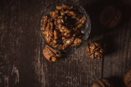top view of shelled walnuts in glass on wooden backdrop