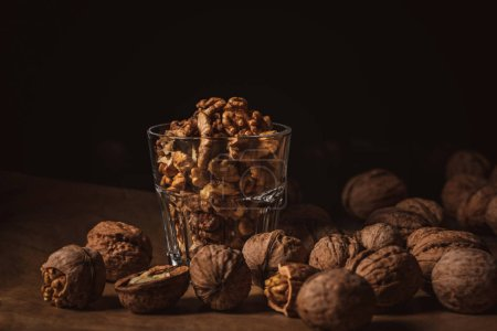 Photo for Close up view of shelled walnuts in glass on black backdrop - Royalty Free Image