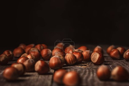 close up view of hazelnuts on wooden surface on black background