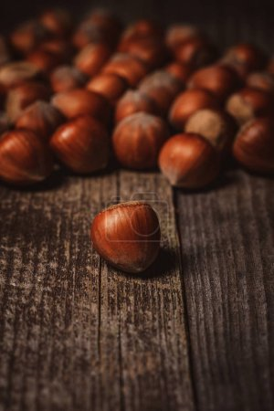 close up view of shelled hazelnuts on wooden backdrop