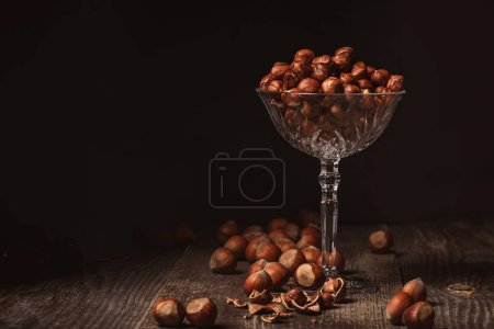 close up view of shelled hazelnuts in glassware on wooden surface on black background