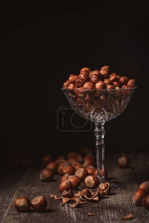 Photo for Close up view of shelled hazelnuts in glassware on wooden surface on black background - Royalty Free Image