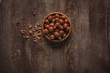 Photo for Top view of hazelnuts in bowl on wooden tabletop - Royalty Free Image