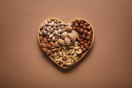 top view of assortment of various nuts in heart shaped box on brown backdrop