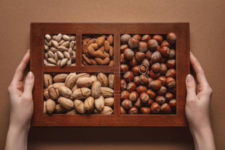 partial view of woman holding box with assortment of different nuts on brown background