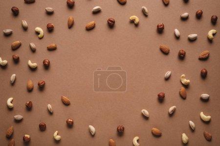 Foto de Marco completo de varios frutos secos dispuestos sobre fondo marrón con espacio vacío en medio - Imagen libre de derechos