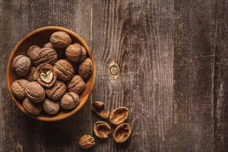 top view of walnuts in bowl on wooden tabletop with husk