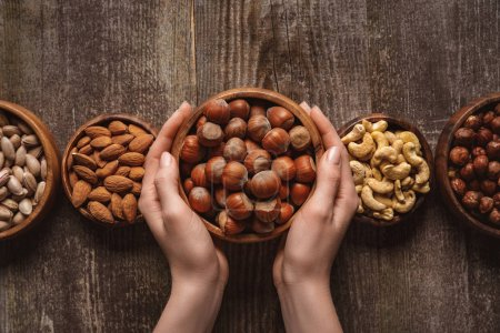 Photo for Partial view of woman holding bowl with hazelnuts on wooden tabletop with different nuts around - Royalty Free Image