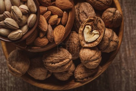 Photo for Top view of almonds, pistachio nuts and walnuts in bowls on wooden surface - Royalty Free Image