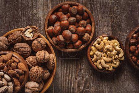Photo for Top view of nuts in bowls arranged on wooden tabletop - Royalty Free Image