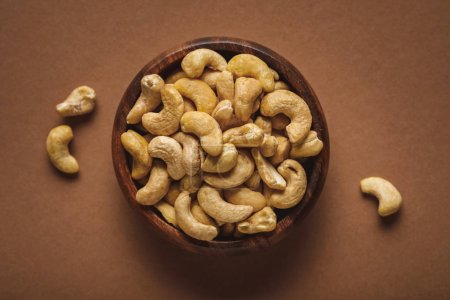 Photo for Top view of cashew nuts in wooden bowl on brown background - Royalty Free Image