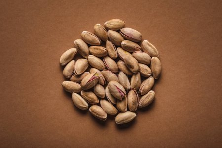 Photo for Top view of pile of pistachio nuts on brown backdrop - Royalty Free Image