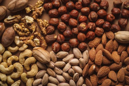 Photo for Flat lay with tasty nuts arrangement on brown background - Royalty Free Image