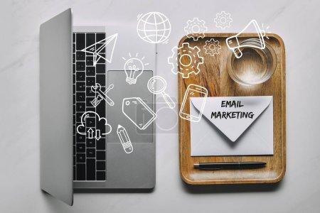 Foto de Plantilla de trabajo con ordenador portátil y bandeja de madera con sobre y agua sobre fondo de mármol blanco con marketing por correo electrónico y los iconos - Imagen libre de derechos