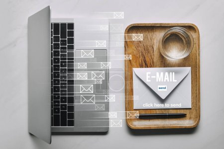 Workplace template with laptop and wooden tray with envelope and water on white marble background with email icons