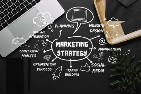 "Smartphone and laptop on black background with ""marketing strategy"" lettering and icons"