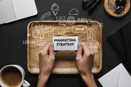 """Photo for Female hands holding business card with """"marketing strategy"""" lettering and icons on black background with tray and stationery - Royalty Free Image"""