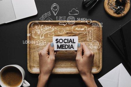 """Foto de Mujer manos sosteniendo tarjetas con letras de """"social media"""" y los iconos en fondo negro con bandeja y papelería - Imagen libre de derechos"""