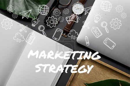 "Flat lay with open notebook and laptop on black background with ""marketing strategy"" lettering and icons"