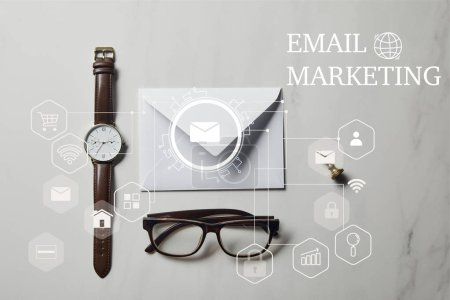 """Letter template with glasses and watch on white marble background with """"Email marketing"""" icons"""
