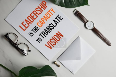 """Card with """"Leadership is the capacity to translate vision"""" lettering, watch and glasses on white marble background with monstera leaves"""