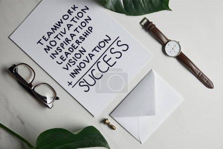 """Tarjeta con inspiración de """"éxito"""", reloj y gafas sobre fondo de mármol blanco con hojas de monstera"""