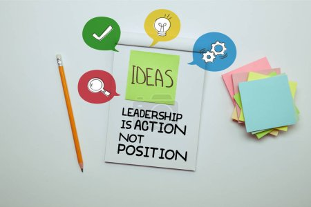 """elevated view of paper sticker with word ideas in notebook with """"Leadership is action, not position"""" lettering and icons"""