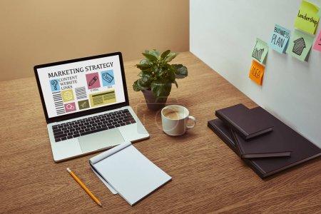 Photo pour Ordinateur portable avec l'inscription «stratégie marketing» et les icônes sur l'écran, cahiers et crayon sur le dessus de table en bois, autocollants sur mur - image libre de droit