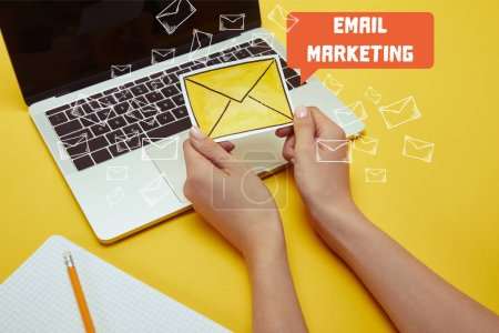 "cropped image of woman holding envelope sign near laptop with ""email marketing"" lettering and email icons"