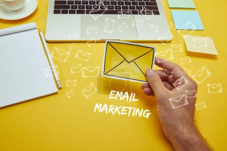 Photo pour Image recadrée de l'homme tenant enveloppe affiche près de l'ordinateur portable avec inscription «email marketing» et les icônes de courriel - image libre de droit