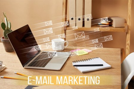 "laptop with email icons and ""email marketing"" lettering on wooden table at home"