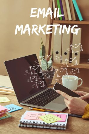 "Photo for Cropped image of woman holding smartphone with email icons and ""email marketing"" lettering at table with laptop and stickers - Royalty Free Image"