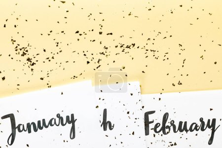 top view of january and february calendar and golden confetti on beige background