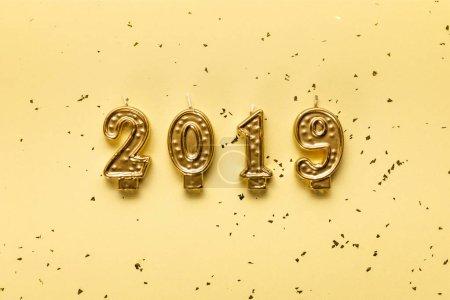 Photo pour Bougies dorées de 2019 et confettis festive sur fond beige - image libre de droit