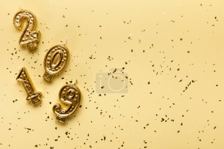2019 numbers candles and golden confetti on beige background