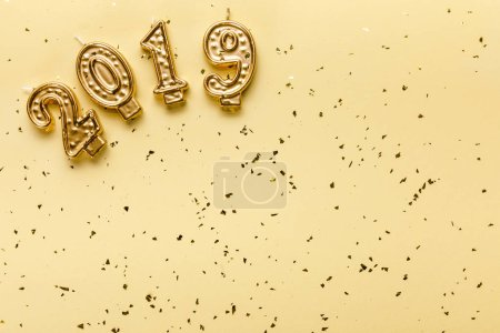 top view of 2019 candles and golden confetti on beige background