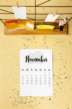 top view of november calendar with golden confetti and cards with clothespins on beige