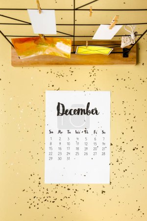 top view of december calendar with golden confetti and cards with clothespins on beige