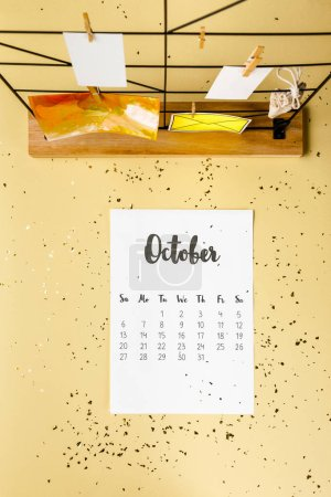 top view of october calendar with golden confetti and cards with clothespins on beige